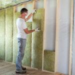 Technicien en train de poser de la mousse isolation sur les murs