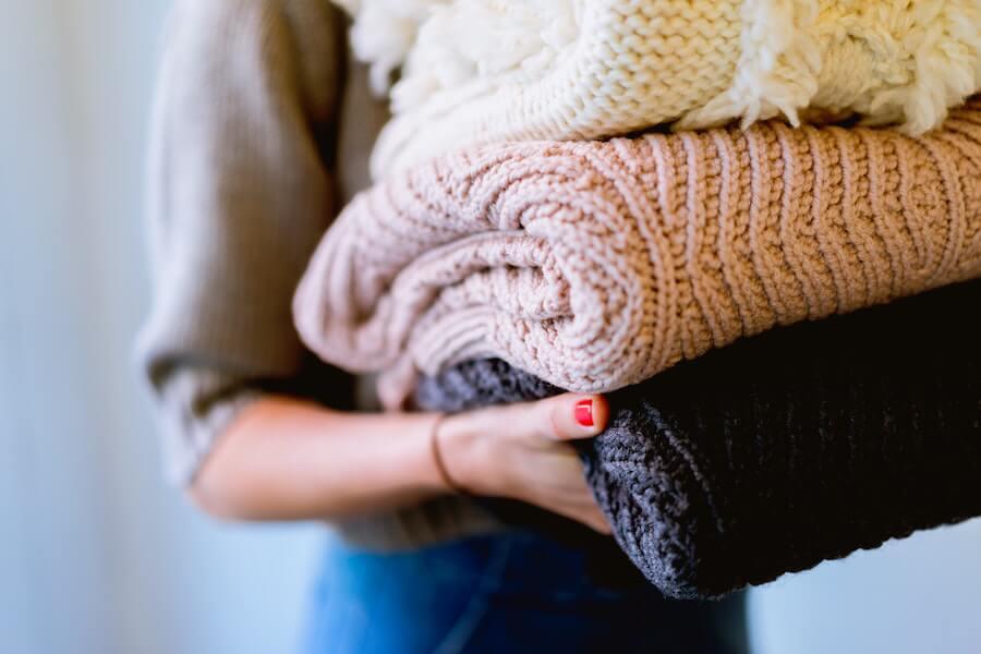 Femme portant une pile de pull-overs dans ses bras
