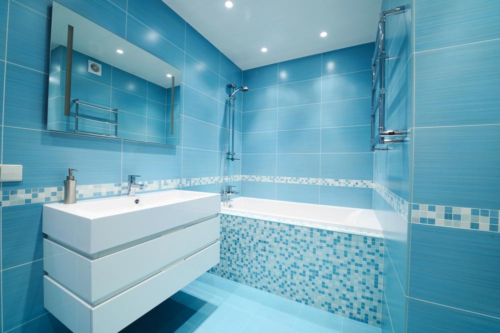 Salle de bain avec faïence bleue sur la baignoire et sur les murs