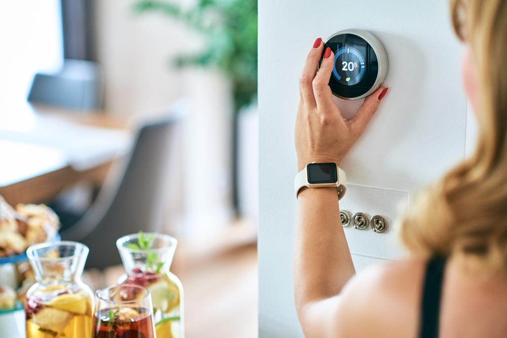 Femme contrôlant la température à son domicile