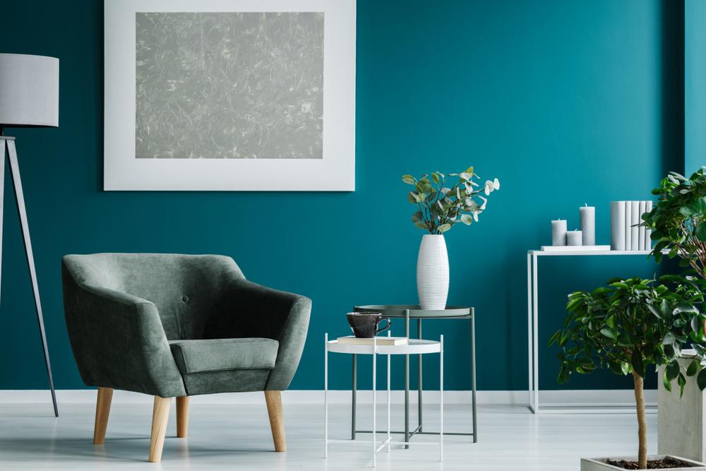 Fauteuil vert contre mur bleu du salon