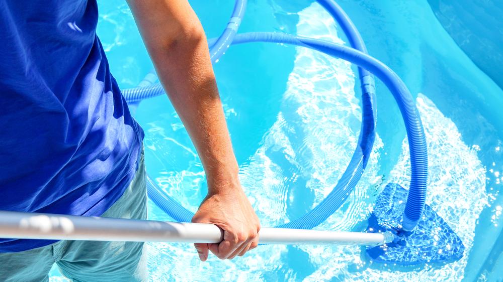 Homme en train d'aspirer une piscine manuellement