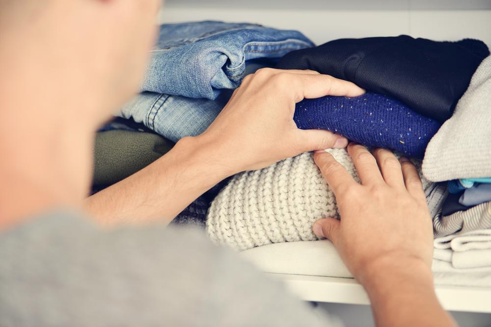 Homme en train de trier ses vêtements posés sur une étagère