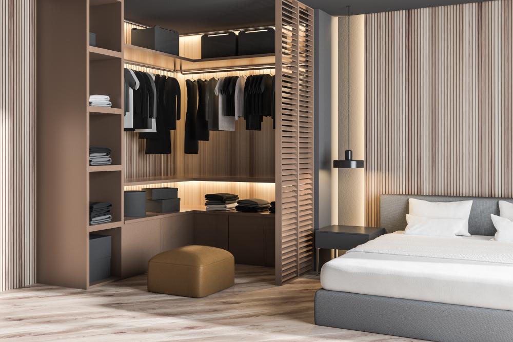 Dressing avec vêtements dans un angle de la chambre parentale avec murs et sol en bois