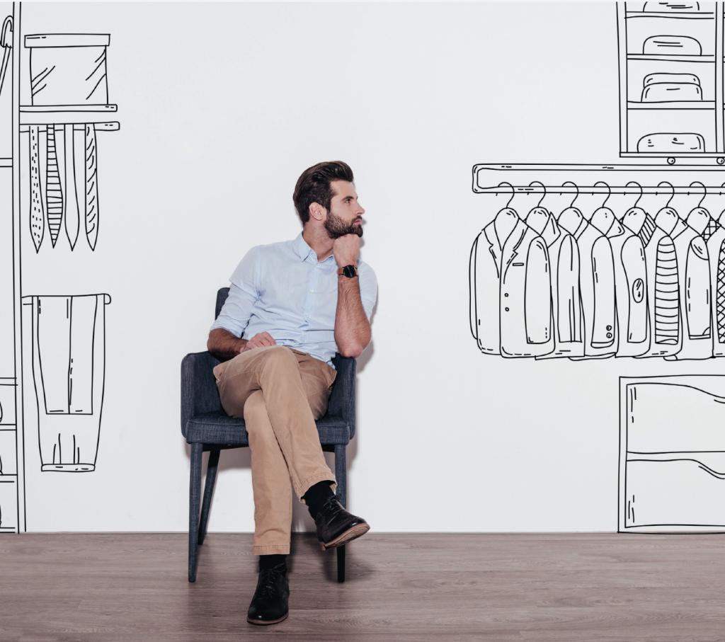 Jeune homme assis avec dessins de penderies et d'étagères sur le mur blanc derrière lui