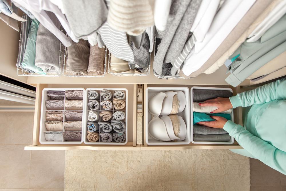 Femme utilisant des et séparateurs pour compartimenter ses tiroirs et gagner de l'espace dans sa garde-robe
